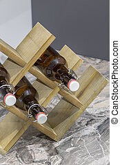 Wooden stand for bottles on the table in the kitchen.