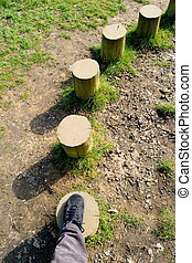 WOODEN STEPPING STONES - Man walking on wooden stepping ...