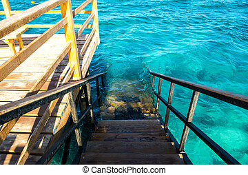 Wooden steps of the pontoon to sea