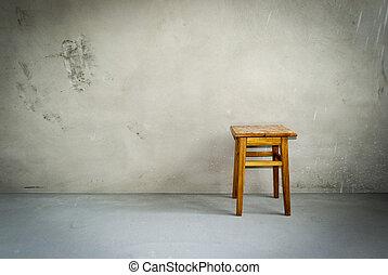 Wooden stool in empty room. Chair on cement floor. Grunge interior.