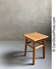 Backless stool in an empty grey room