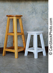 Wooden stools with cement wall.