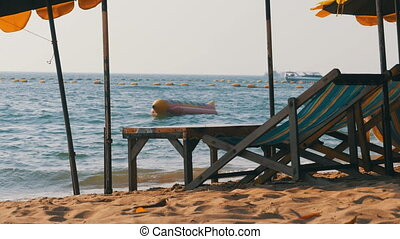 Wooden Sun Beds with Umbrella on a Sandy Beach against the...