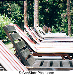 Wooden sun loungers by the swimming pool on a summer day