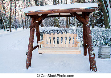 Wooden swing bench in the Park in winter