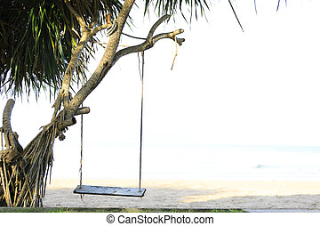 wooden swing chair hanging on tree near beach, Thailand.