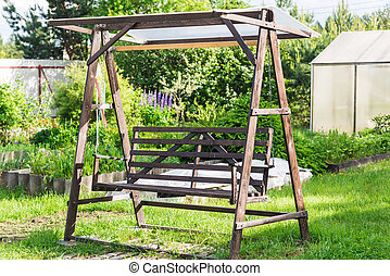 wooden swing in the garden on the grass