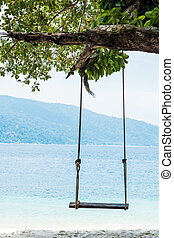 Wooden swing on the beach