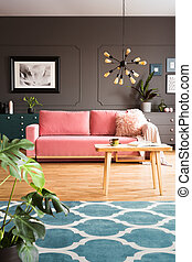 Wooden table and blue carpet in grey living room interior with poster and pink couch. Real photo