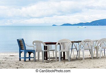Wooden table and chair set on white beach sand and blue sea in sunny day