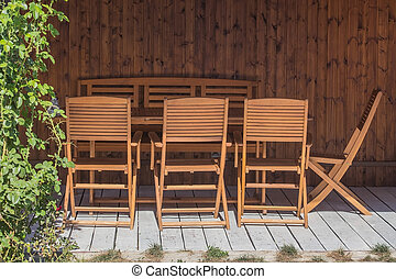 Wooden table and chairs under a canopy