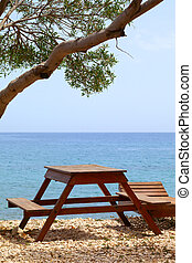 Wooden table and deck chair on summer resort at sun day