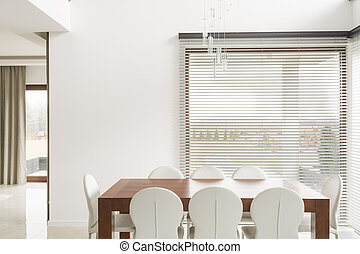 Wooden table and white chairs in dining room