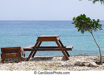 Wooden table, deck chair and clear sea on summer resort