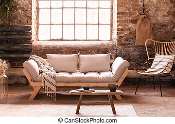 Wooden table in front of grey sofa in living room interior with armchair and window. Real photo