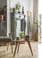 Wooden table next to grey armchair in retro living room interior with plants. Real photo