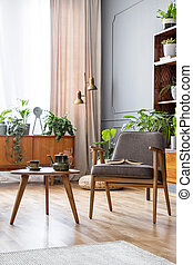 Wooden table next to grey armchair in vintage living room interior with plants. Real photo