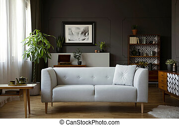 Wooden table next to grey sofa in dark living room interior with poster and plants. Real photo