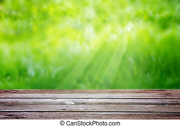 Wooden table on a background of blurred green grass with sun rays. Template, element for advertising