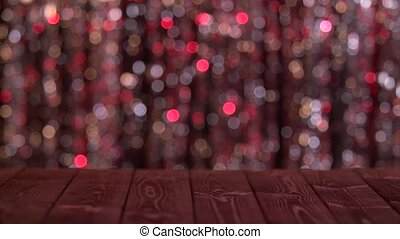 Wooden table on the screen of shimmer abstract blurred red...