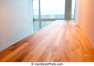 Wooden table top with blurred window background