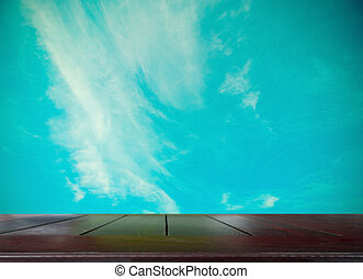 wooden table top with vintage tone sky background