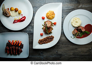 wooden table topped with white plates with different types of food in restaurant