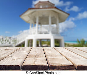 Wooden table with a nice wedding tower and beach background, vacation concept