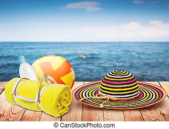 Wooden table with beach items, blur sea on background, template