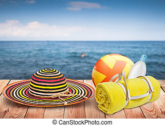 Wooden table with beach items, blur sea on background, template design