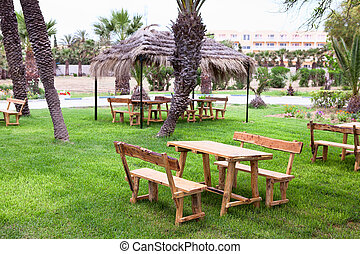 Wooden table with benches in tropical green garden