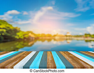 wooden table with blur image of lake.