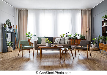 Wooden table with flowers between armchairs in spacious living room interior with sofa. Real photo
