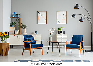 Wooden table with flowers between blue armchairs in grey flat interior with posters. Real photo
