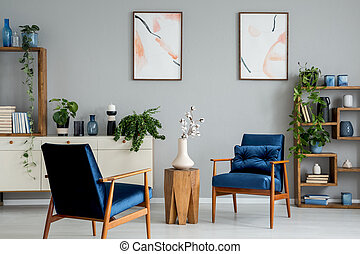 Wooden table with flowers between blue armchairs in grey interior with posters and plants. Real photo