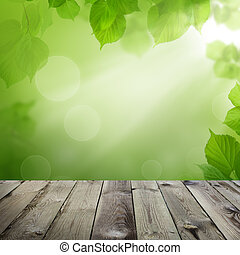 Wooden table with green leaves and abstract bokeh light background