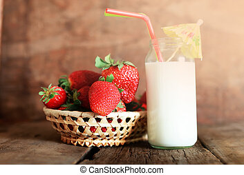 wooden table with strawberries and milk in a glass