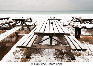 Wooden tables covered by snow