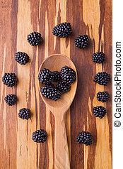 Wooden tablespoon with blackberries. Berries arranged around...