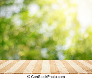 Wooden tabletop with fresh green nature blurred background