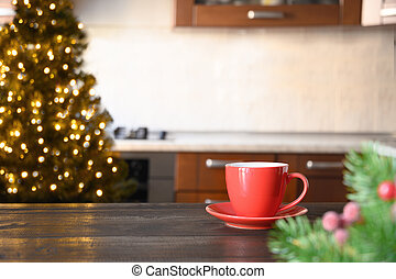 Wooden tabletop with red cup of coffee and blurred Christmas kitchen.