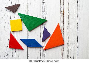 wooden tangram on white wood background