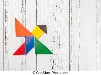 wooden tangram shaped like a flying bird with copy space