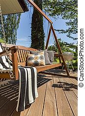 Wooden terrace with a garden swing