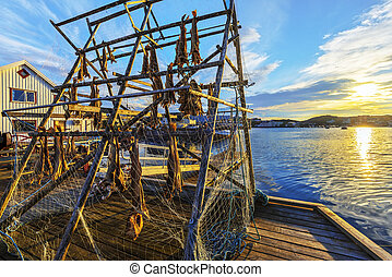 Wooden terrace with cod fish drying rack illuminated with evening sun in the border of Barents Sea. The picture is taken in fishers village Gjesvaer in the west of Mageroya Island. Nordkapp Municipality in Norwegian Finnmark county.