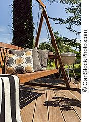 Wooden terrace with garden swing