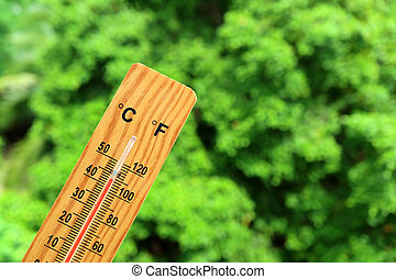 Wooden thermometer against green foliage in the sun showing very high temperature