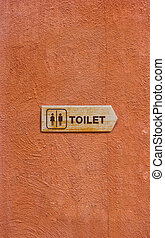 Wooden Toilet Sign on The Orange Wall