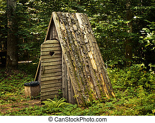 wooden toilet with opened door in the forest