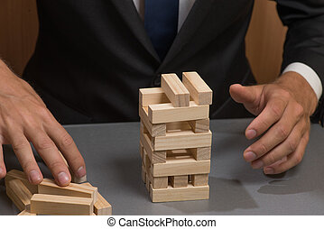 Wooden tower blocks, the hand of the businessman. Risks and planning